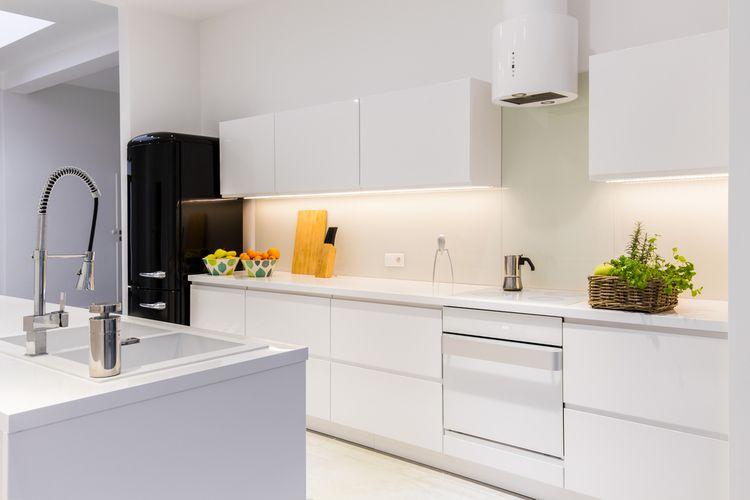 Biela kuchyňa s čiernou chladničkou