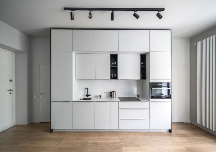 Malá biela kuchyňa s čiernymi doplnkami