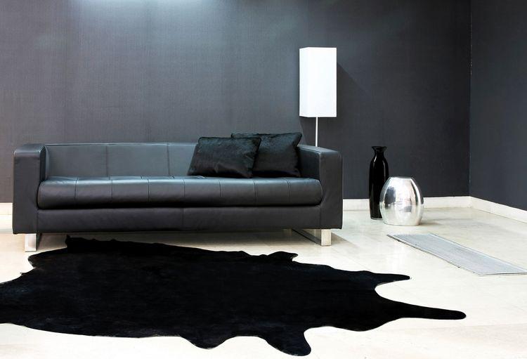 Čierny gauč, koberec a stena