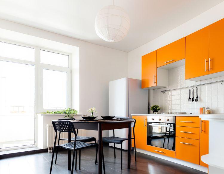 Oranžovo-biela kuchyňa s čiernym sedením