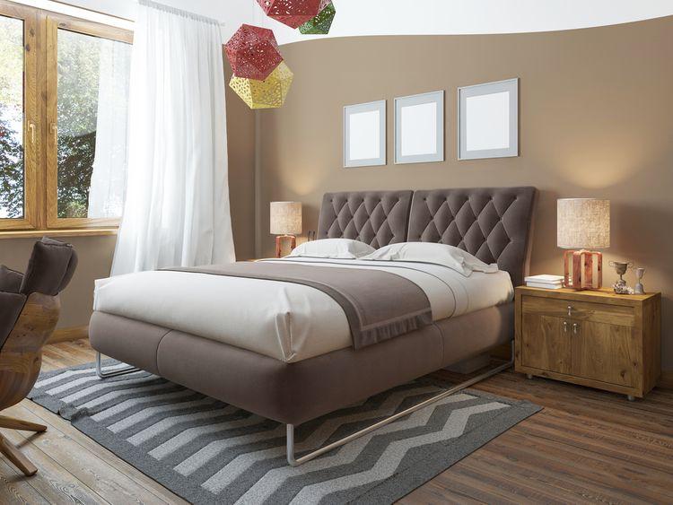 Spálňa s hnedými stenami a farebným lustrom