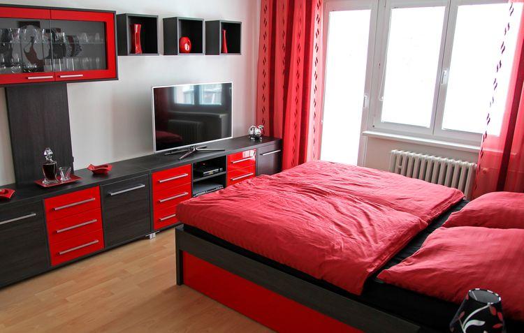 Sivo-červený lesklý nábytok a posteľ s červenými perinami