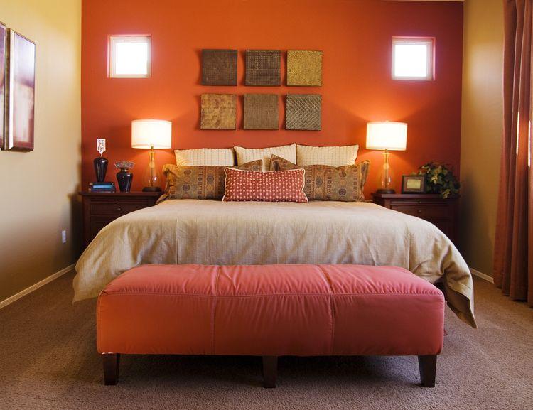 Spálňa s matnočervenou stenou a veľkou posteľou