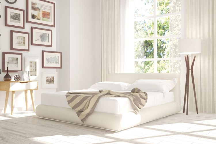 Minimalistická spálňa s bielou posteľou, dreveným stolíkom a obrazmi