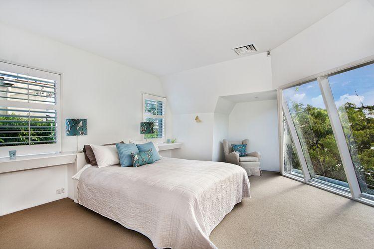 Moderná podkrovná biela spálňa s modrými detailmi
