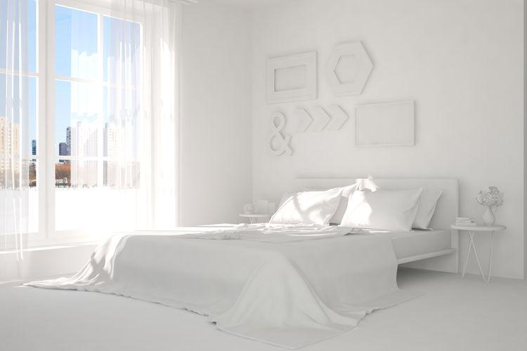 Spálňa s bieľou posteľou, stenami a obrazmi