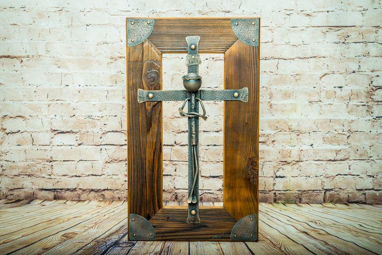 Kovový kríž v drevenom ráme