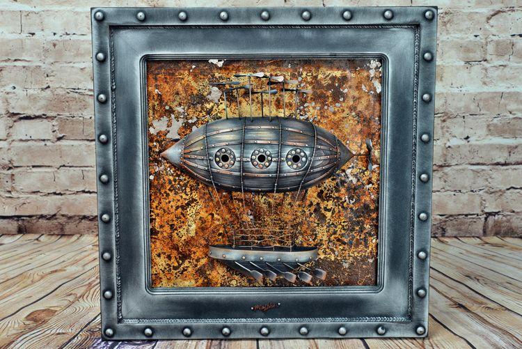 Kovová vzducholoď na drevenom podklade a v kovovom ráme